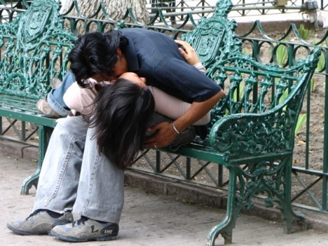 Two persons kissing on a bench, while one person lays on the other person's legs.