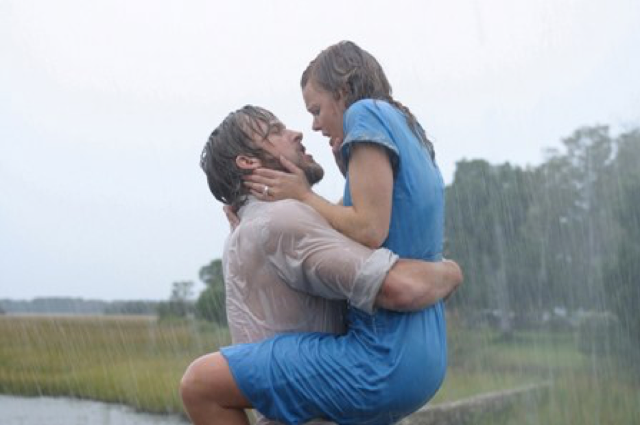 A man carrying a woman. They are face to face, under the rain.