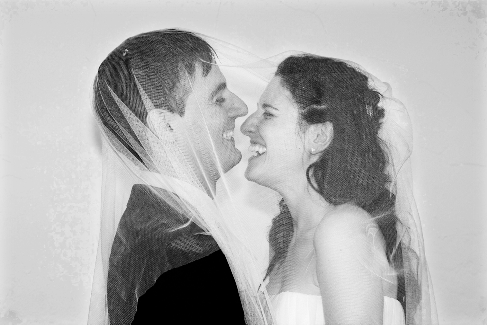 Two persons smiling at each other, face to face. They are wrapped under the woman's wedding veil.