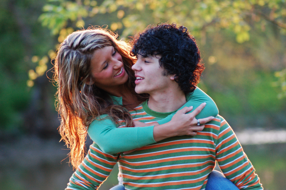 Two persons looking at each other and smiling. The woman is hugging the other person from behind.