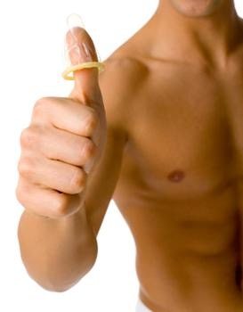 A shirtless person with a condom on their thumb.