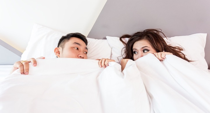 Two people lying next to each other underneath a blanket.