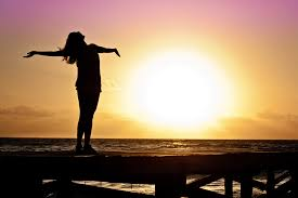 A person with their arms wide open in front of a sunset.