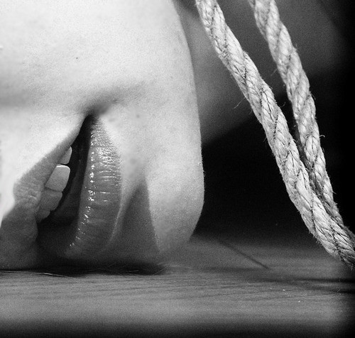 A person's chin on the floor. There is rope hanging from their neck.