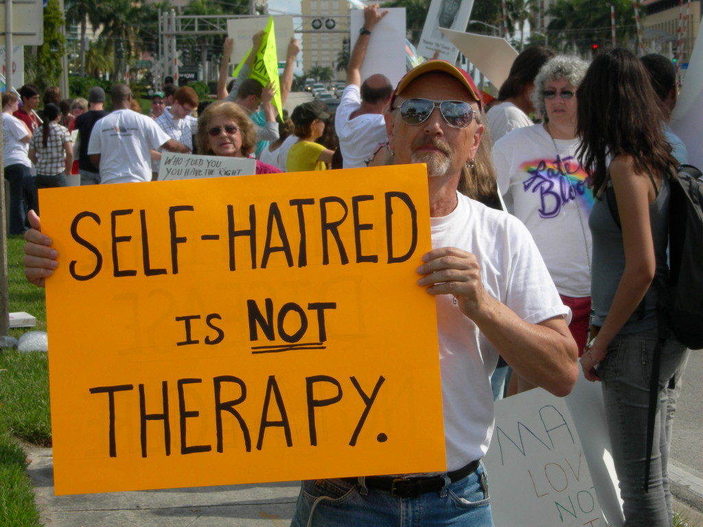 """A person holding a sign that says """"self-hatred is not therapy."""""""
