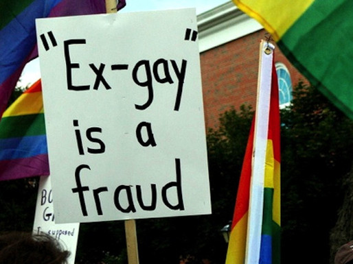 """A sign that says """"Ex-gay is a fraud."""" There are LGBTQ colorful flags around the sign."""