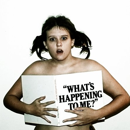 """Person using a book """"What's Happening to Me?"""" to cover their chest."""