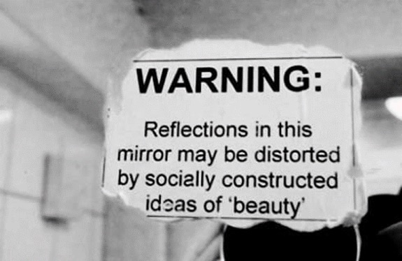 """Mirror with a note that says """"WARNING: Reflections in this mirror may be distorted by socially constructed ideas of 'beauty'"""""""