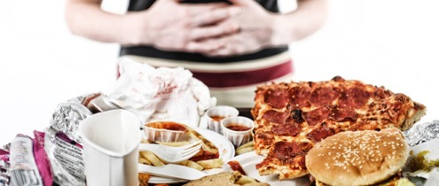 A person holding their stomach behind a variety of foods: pizza, fries, and a burger.