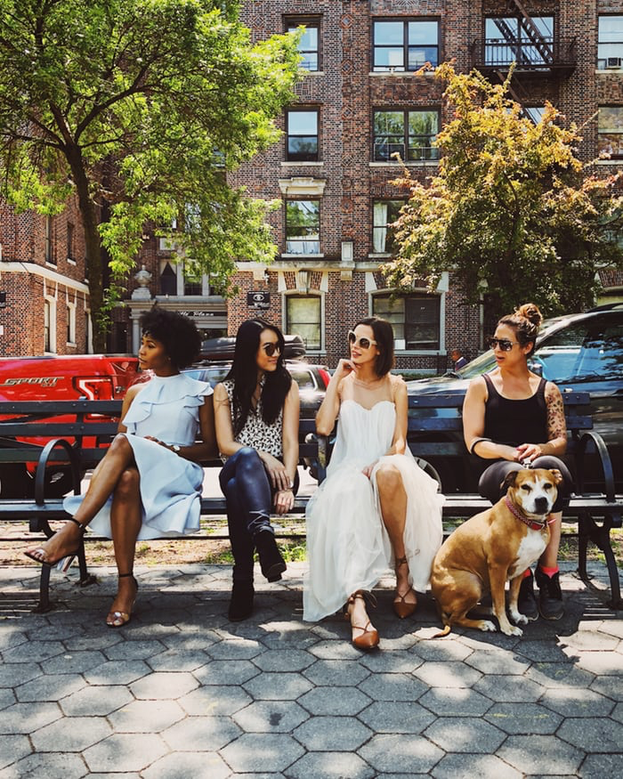 Four people sitting on a bench next to a dog.