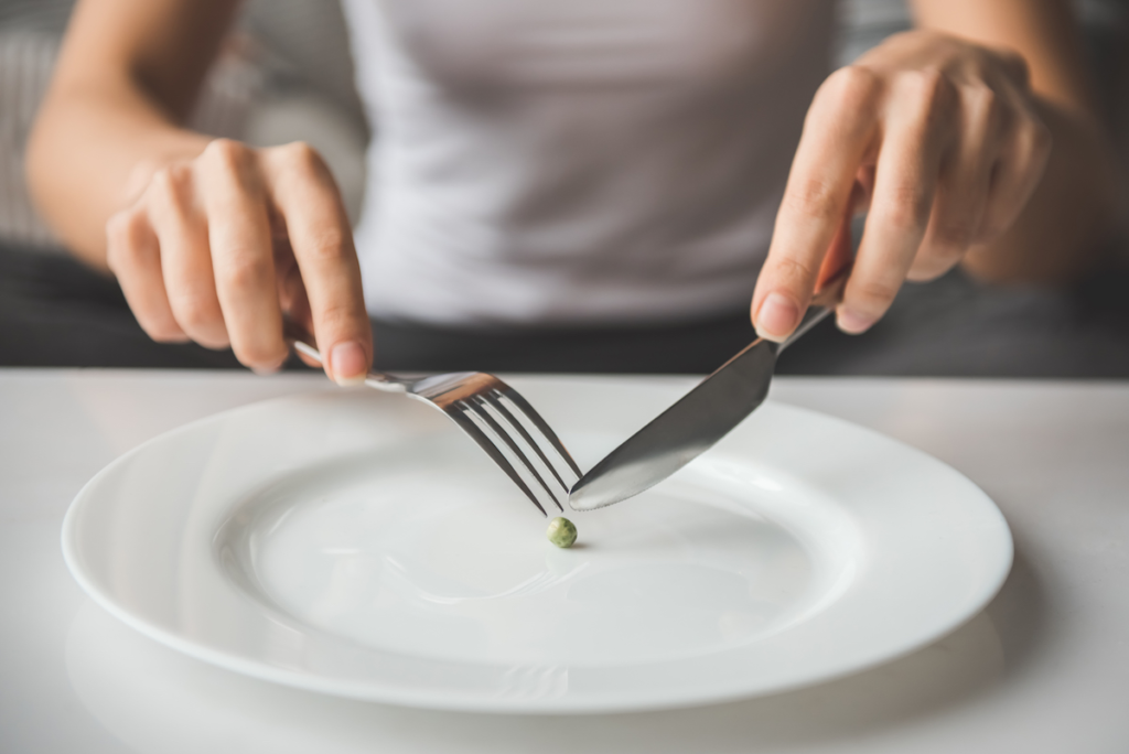 A person holding a fork and a knife over a white plate.