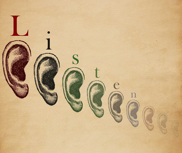 """Ears aligned nect to each other. The word """"listen"""" is placed above the ears."""
