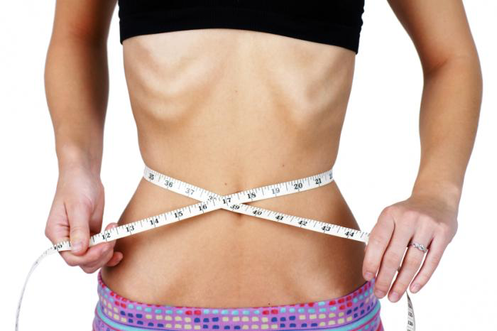 A person measuring their bare abdomen with a measuring rope. The person's ribs are sticking out.