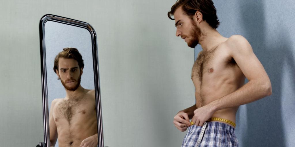 A slim man looking at himself in a mirror.
