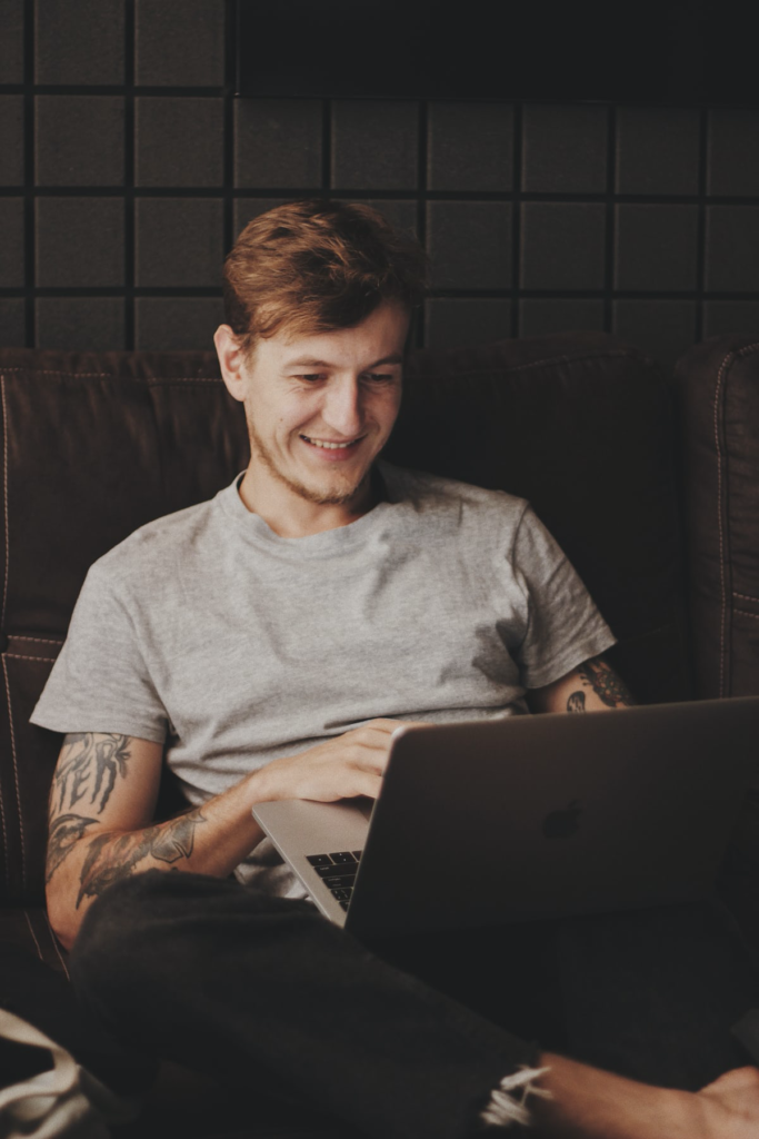 A person holding a computer and smiling at it.