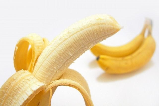 A peeled banana and a couple of bananas.
