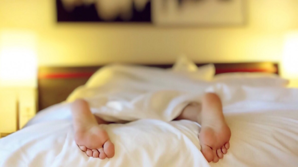 A person is lying down with only their feet soles showing.