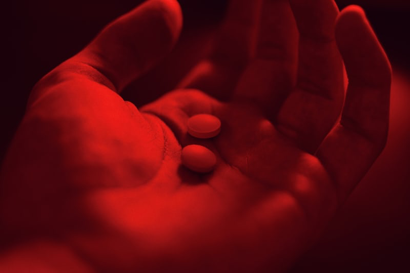 A hand holding two medicinal tablets.