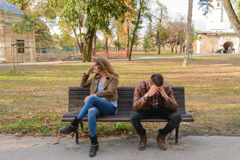 A couple sitting on a bench. One person is facing away and the other has their head down.