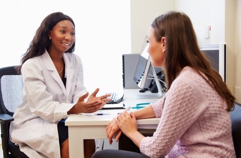 A doctor talking to a client. They are sitting across from each other.