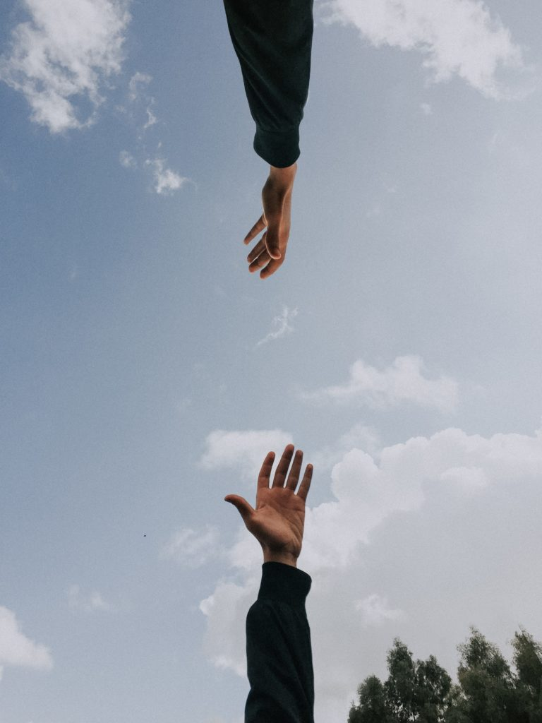 Two hands reaching toward each other.