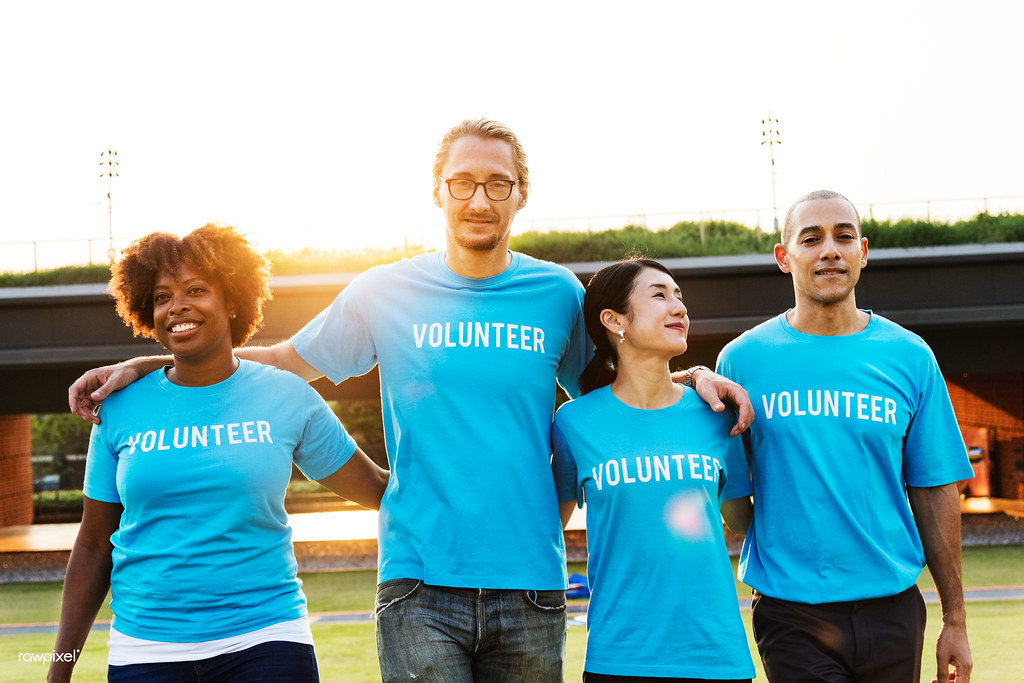 """A group of four persons wearing shirts that say """"volunteer."""""""