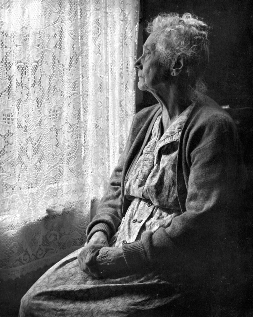 An older person looking out a window.