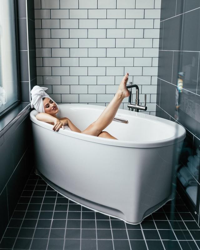 A person in a bathtub, pointing their leg up.