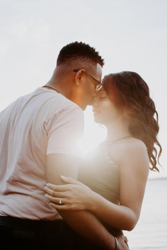 Two persons facing each other. One person is kissing their partner's nose.