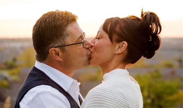 Two persons kissing on the mouth.