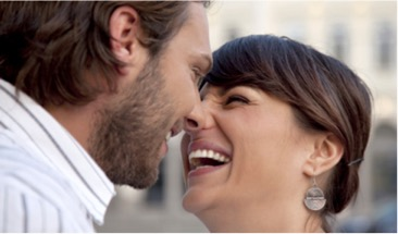 Two persons facing each other and smiling.