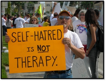 """A man holding a sign that states """"Self-hatred is not therapy."""""""