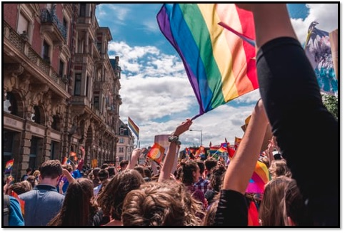 A crowd of people, one person is holding a rainbow flag.