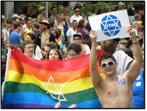 A crowd of people holding a rainbow flag with a star of david. A man is also holding up a paper with the star of david.