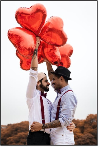 Two men holding each other and holding heart balloons.
