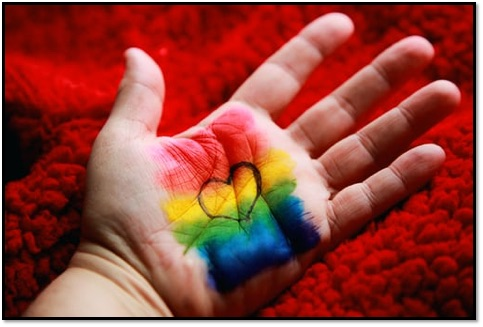 A hand painted in rainbow with a heart on it.