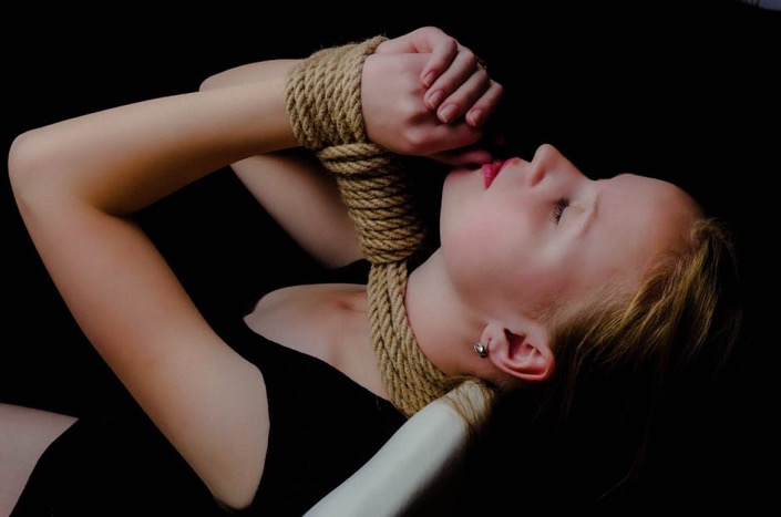 A person tied by the neck with a rope. The person's wrists are also tied with the rope.