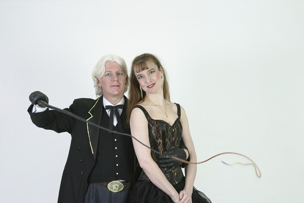 A couple standing next to each other. The man is holding a long whip and is wearing black gloves.