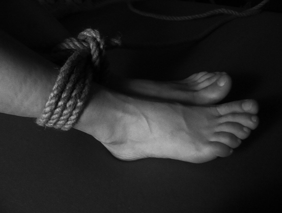 A persons feet tied with rope.