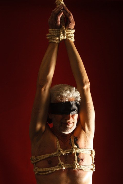 A blindfolded person with their wrists tied with rope. Their chest is also wrapped with rope.