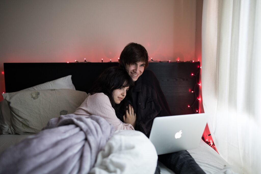 A couple cuddling and starring at a laptop screen.