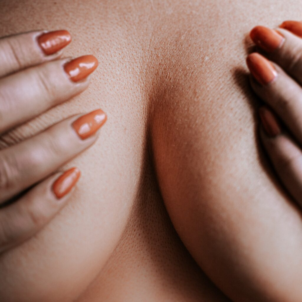 A person holding their breasts.