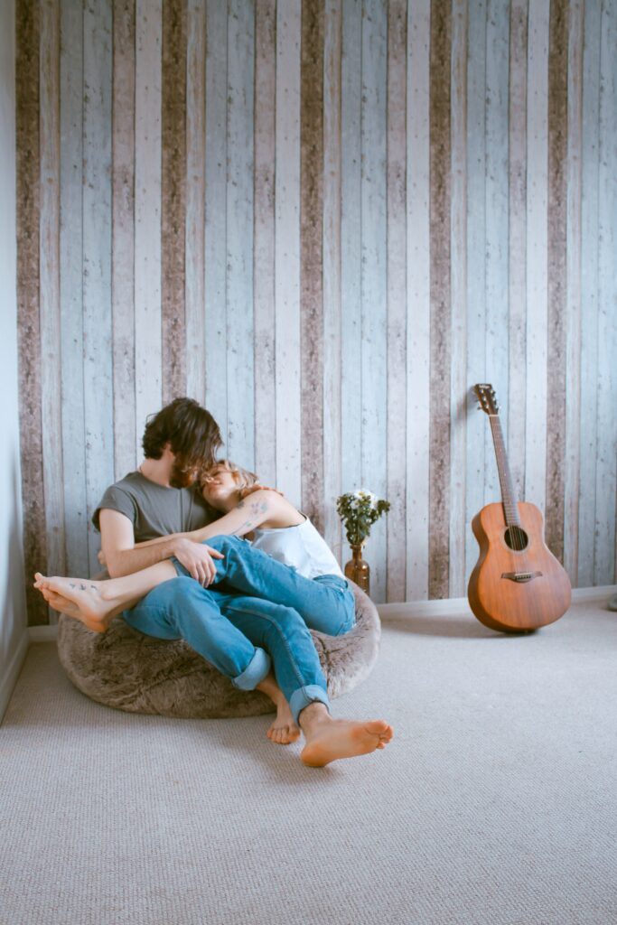A couple sitting on a bean bag, while hugging.