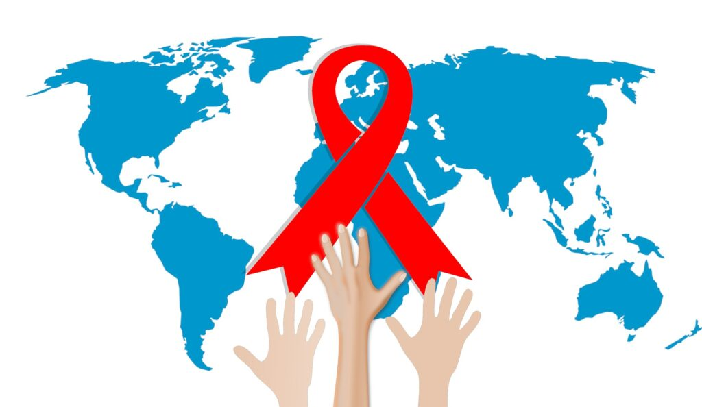 A red ribbon on top of a world map. There are hands reaching toward the red ribbon.