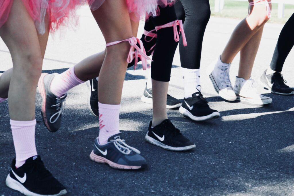 People running with pink ribbons on their legs.