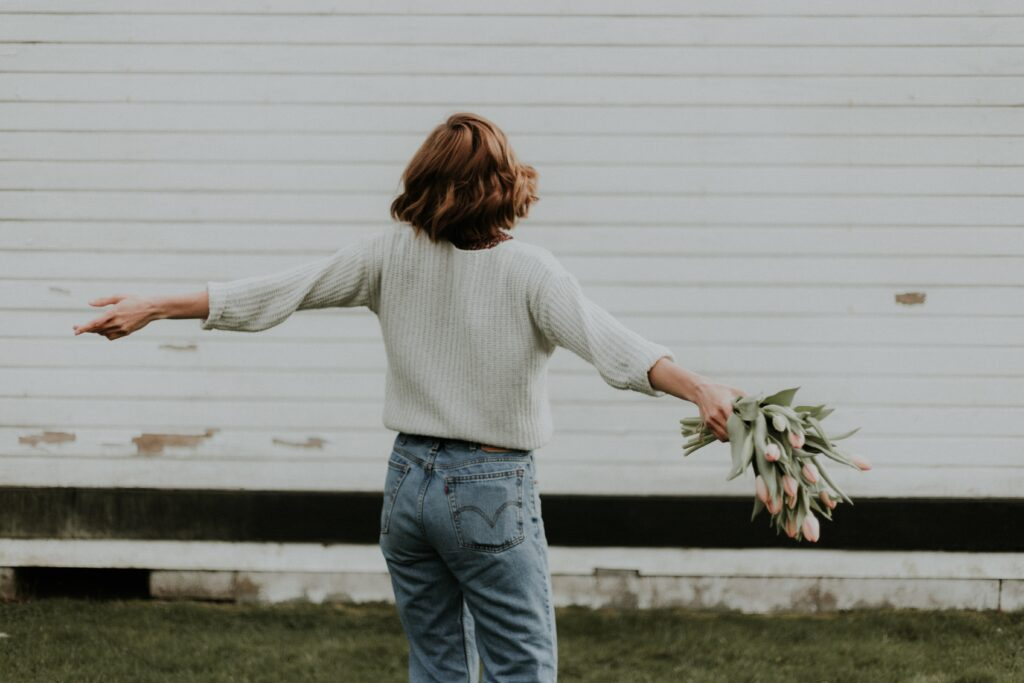 A person holding flowers and extending their arms.