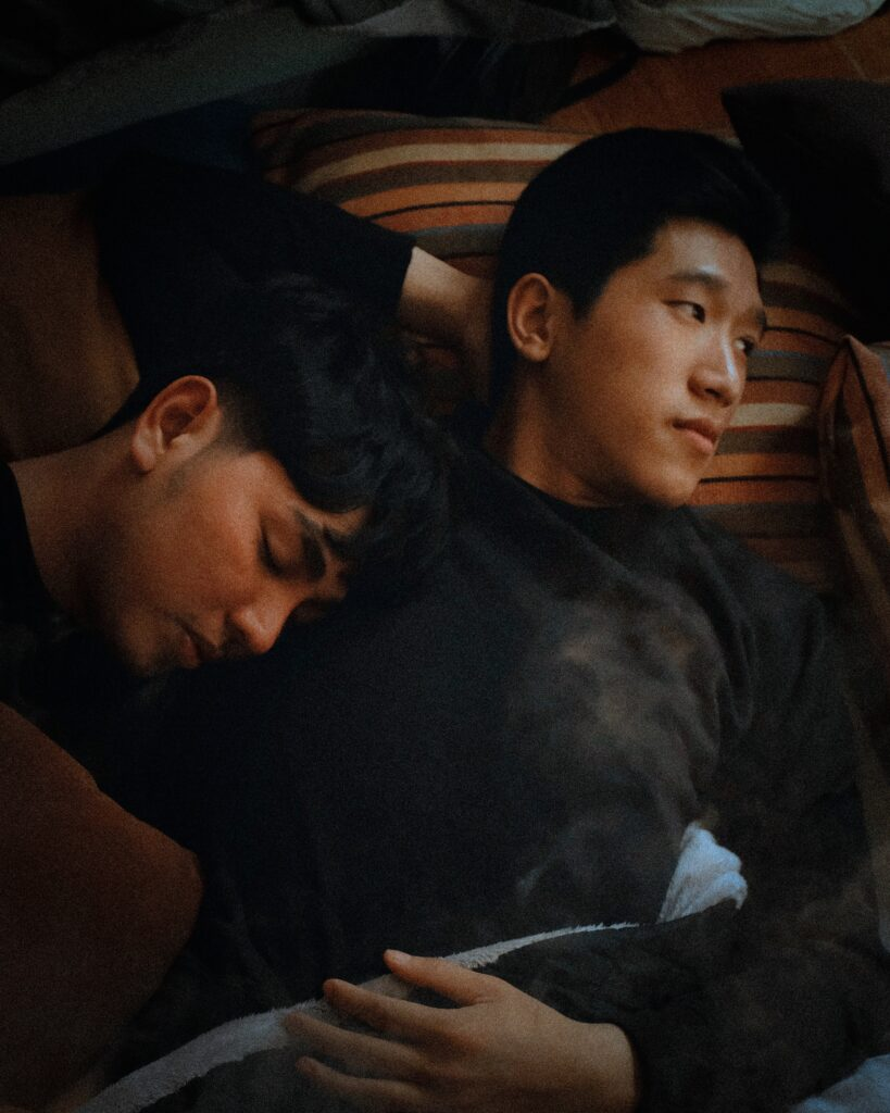 A couple laying on a bed together.