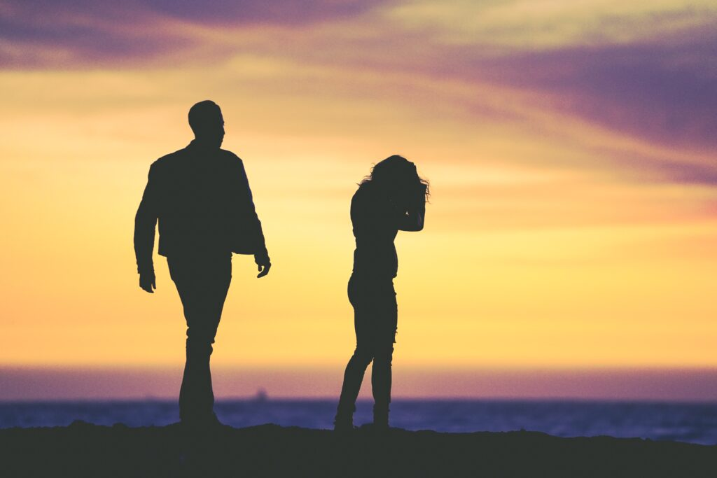 Silhouette of a couple facing away from each other.