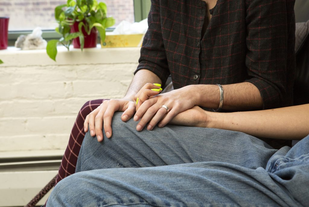 Two persons holding hands.
