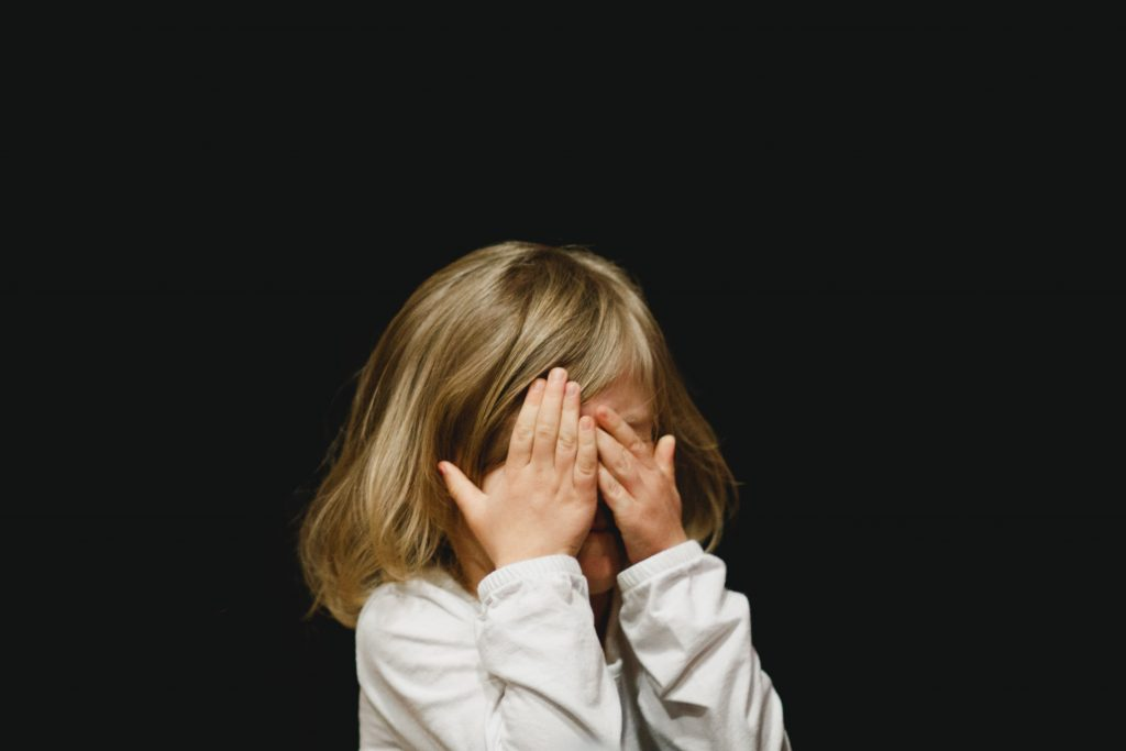 A child covering their face with both of their hands.